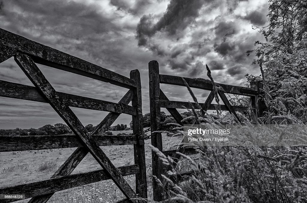 Locked Wooden Gate On Field Against Cloudy Sky : Stock Photo