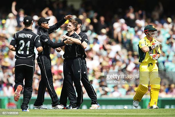 Lockie Ferguson of New Zealand celebrates with team mates after taking the wicket of David Warner of Australia during game one of the One Day...