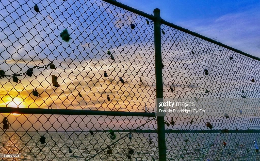Locks On Fence By Sea Against Sky During Sunset : Stock Photo