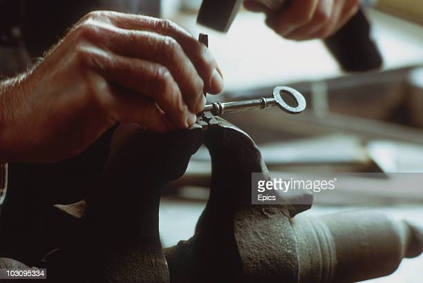 Locksmith at work making a key at the Lock Museum in the town of Willenhall, Dudley which is famous for making locks since the industrial revolution,...