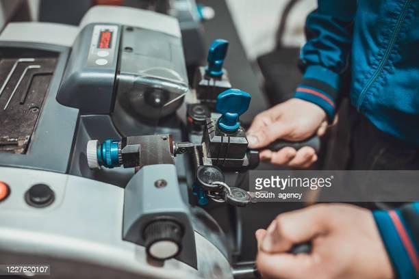 locksmith taglia chiave auto con la sua macchina - ripetizione foto e immagini stock