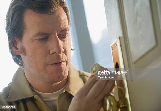 locksmith repairing door lock - locksmith stockfoto's en -beelden
