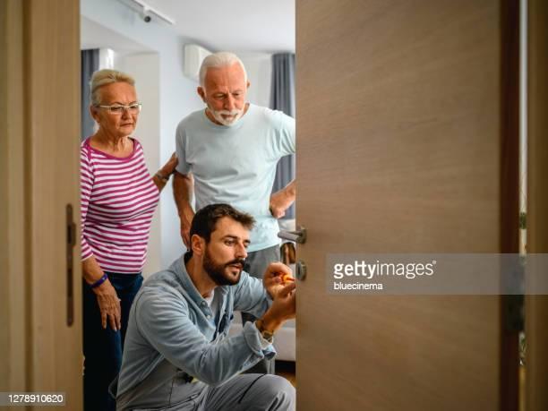 slotenmaker die met slot van de huisdeur werkt gebruikend schroevendraaier - locksmith stockfoto's en -beelden