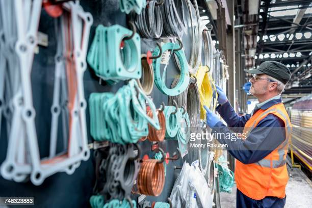 Locomotive engineer picking gaskets and seals in train works