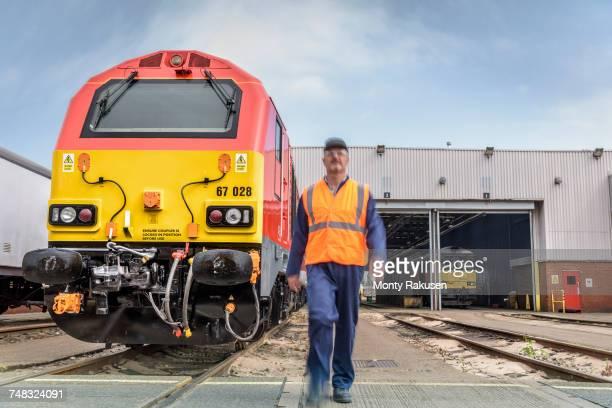 Locomotive engineer walking by locomotive in train works