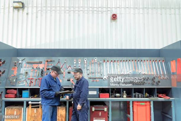 Locomotive engineers in discussion and picking tools in train works