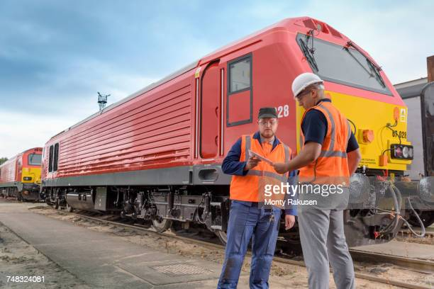 Locomotive engineers in discussion beside locomotive in train works
