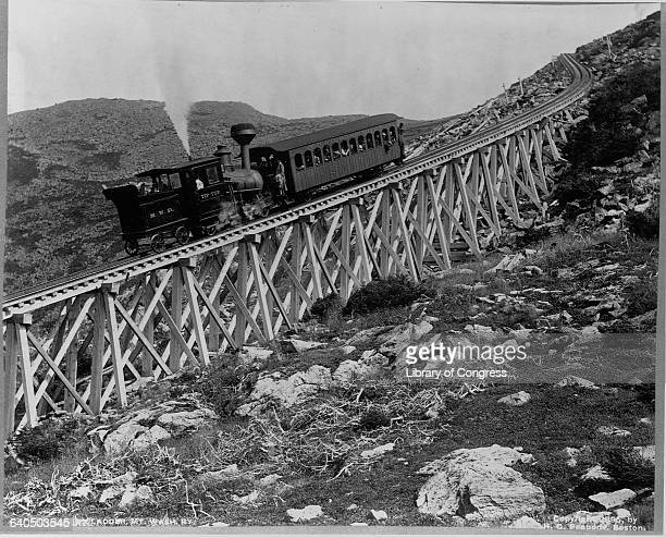 A locomotive pushes a passenger car up Jacob's Ladder a steep railroad bridge on Mount Washington in New Hampshire 1895