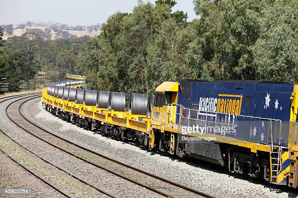 locomotive with trainload of coiled steel in hills - rail freight stock pictures, royalty-free photos & images