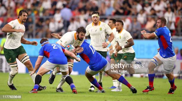Lodewyk de Jager of South Africa is tackled by Louis van der Westhuizen and Andre Rademeyer of Namibia during the Rugby World Cup 2019 Group B game...
