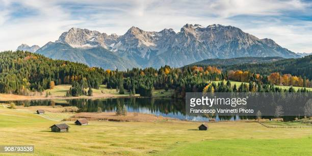 Lodges with Gerold lake and Karwendel Alps in the background. Krün, Upper Bavaria, Bavaria, Germany.