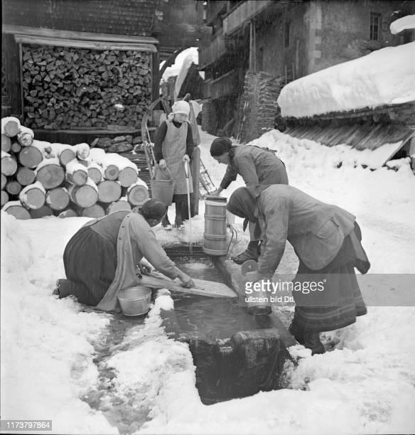 Loetschental women clean milk churn at fountain 1941