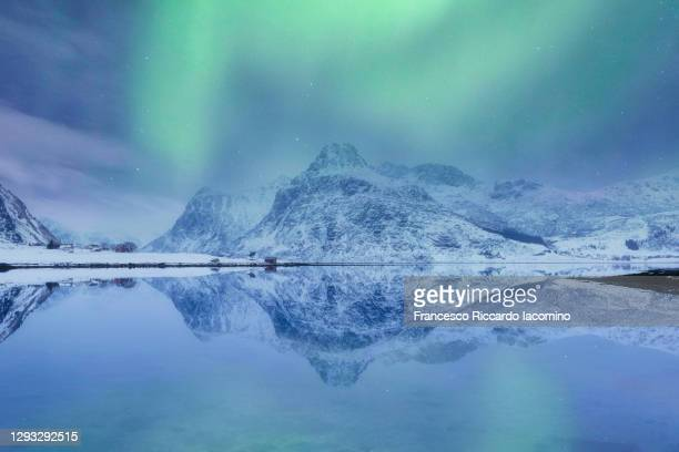 lofoten islands, norway. aurora borealis over the lake and landscape mirroring - norway stock pictures, royalty-free photos & images