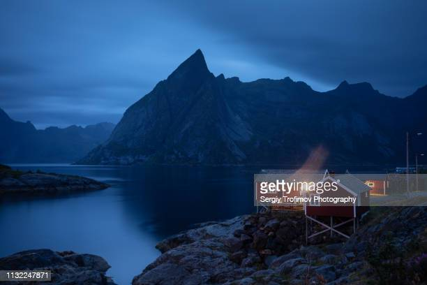 Lofoten landscape at night, light in window of rorbuer, Hamnoy, Norway