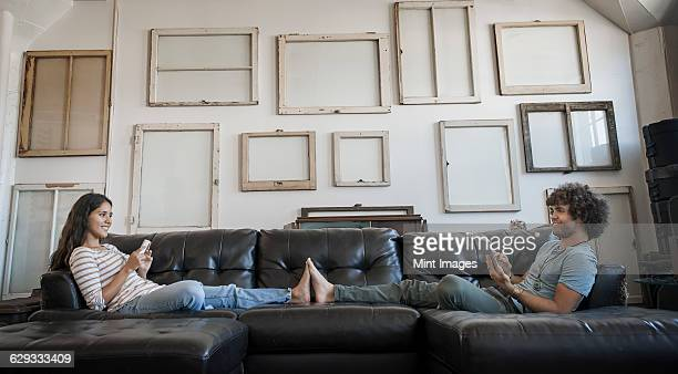 loft decor. a wall hung with pictures in frames, reversed to show the backs. a young couple sitting on the sofa feet touching, one using a smart phone and one holding a digital tablet. - afro americano - fotografias e filmes do acervo
