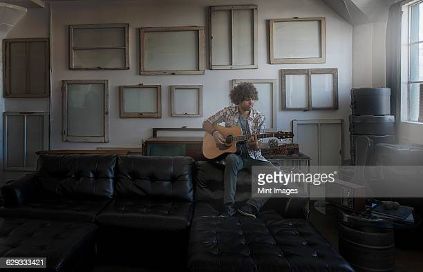 Loft decor. A wall hung with pictures in frames, reversed to show the backs. A man playing a guitar.