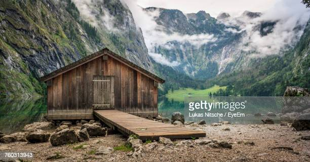 log cabin by obersee lake amidst mountain during foggy weather - cabaña fotografías e imágenes de stock