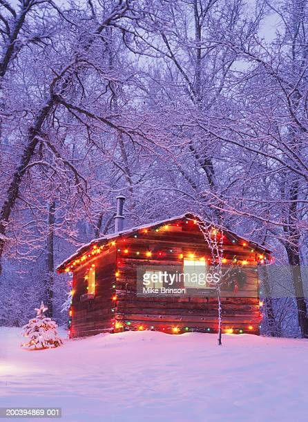 Log cabin exterior decorated with Christmas lights, winter, dusk