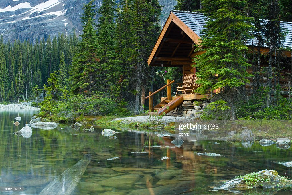 Log cabin hidden in the trees by the Lake Ohara in Canada : Stock Photo