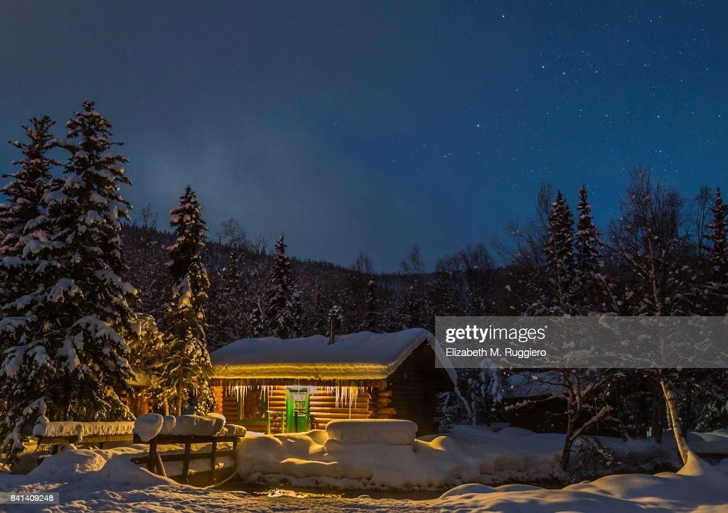 Log Cabin Eingebettet In Wäldern An Verschneiten Winterabend Stock