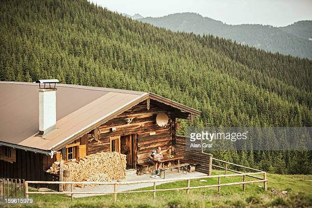 Log cabin on grassy hillside