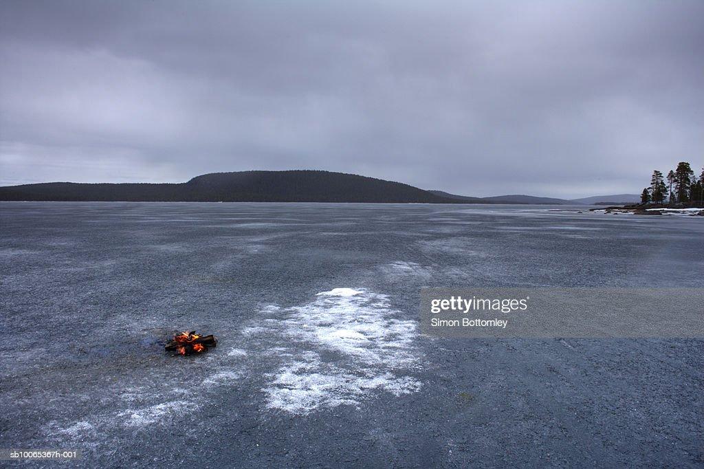 Log fire burning on frozen lake : Foto stock