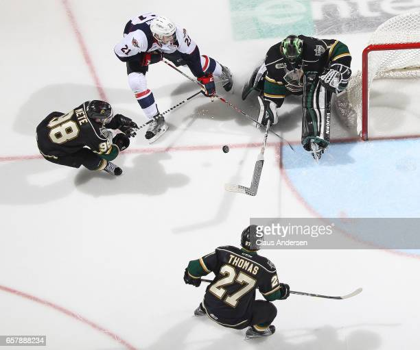 Logan Brown of the Windsor Spitfires tries to get a shot past Tyler Parsons of the London Knights during Game One of the OHL Western Conference...