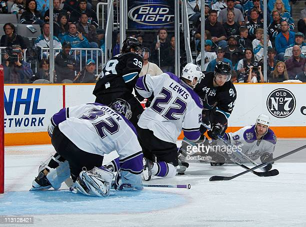 Logan Couture and Marc-Edouard Vlasic of the San Jose Sharks look for a rebound against Ryan Smyth, Trevor Lewis and Jonathan Quick of the Los...