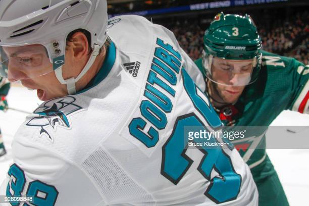Logan Couture of the San Jose Sharks and Charlie Coyle of the Minnesota Wild battle for the puck during the game at the Xcel Energy Center on...