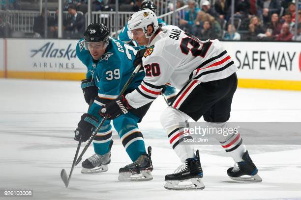 Logan Couture of the San Jose Sharks defends Brandon Saad of the Chicago Blackhawks at SAP Center on March 1 2018 in San Jose California