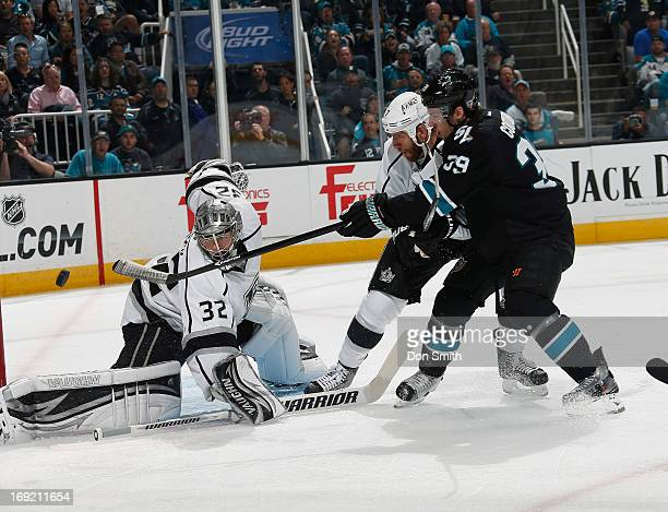 Logan Couture of the San Jose Sharks fires a shot against Jonathan Quick and Rob Scuderi of the Los Angeles Kings in Game Four of the Western...