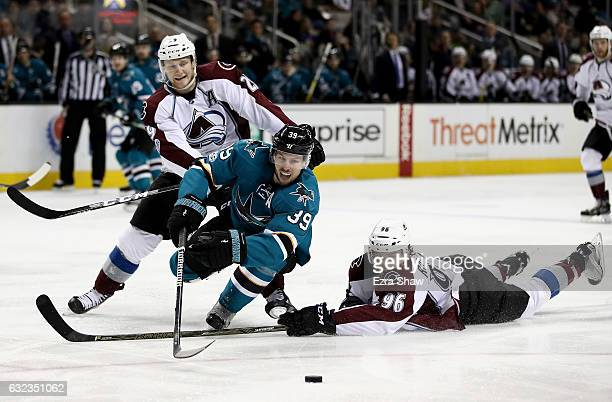 Logan Couture of the San Jose Sharks goes for the puck against Mikko Rantanen and Nathan MacKinnon of the Colorado Avalanche at SAP Center on January...
