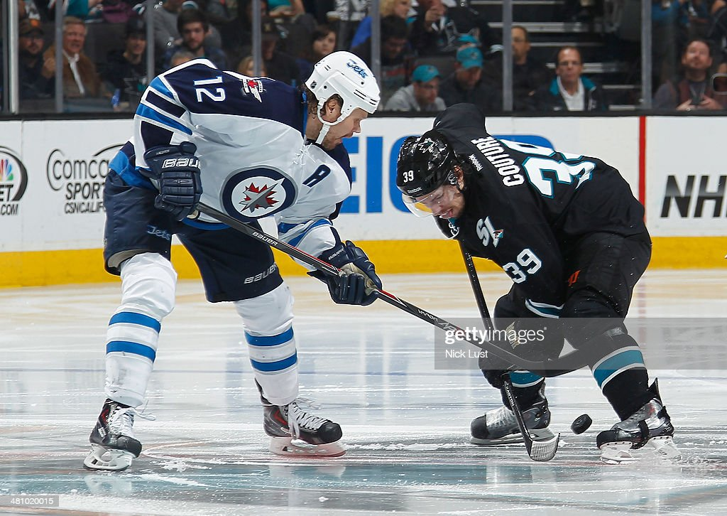 Logan Couture #39 of the San Jose Sharks has a face-off against Olli Jackson #12 of the Winnipeg Jets during an NHL game on March 27, 2014 at SAP Center in San Jose, California.