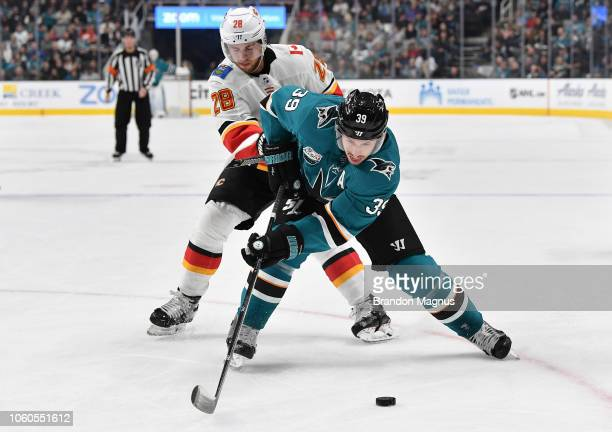 Logan Couture of the San Jose Sharks keeps the puck away from Elias Lindholm of against the Calgary Flames at SAP Center on November 11 2018 in San...