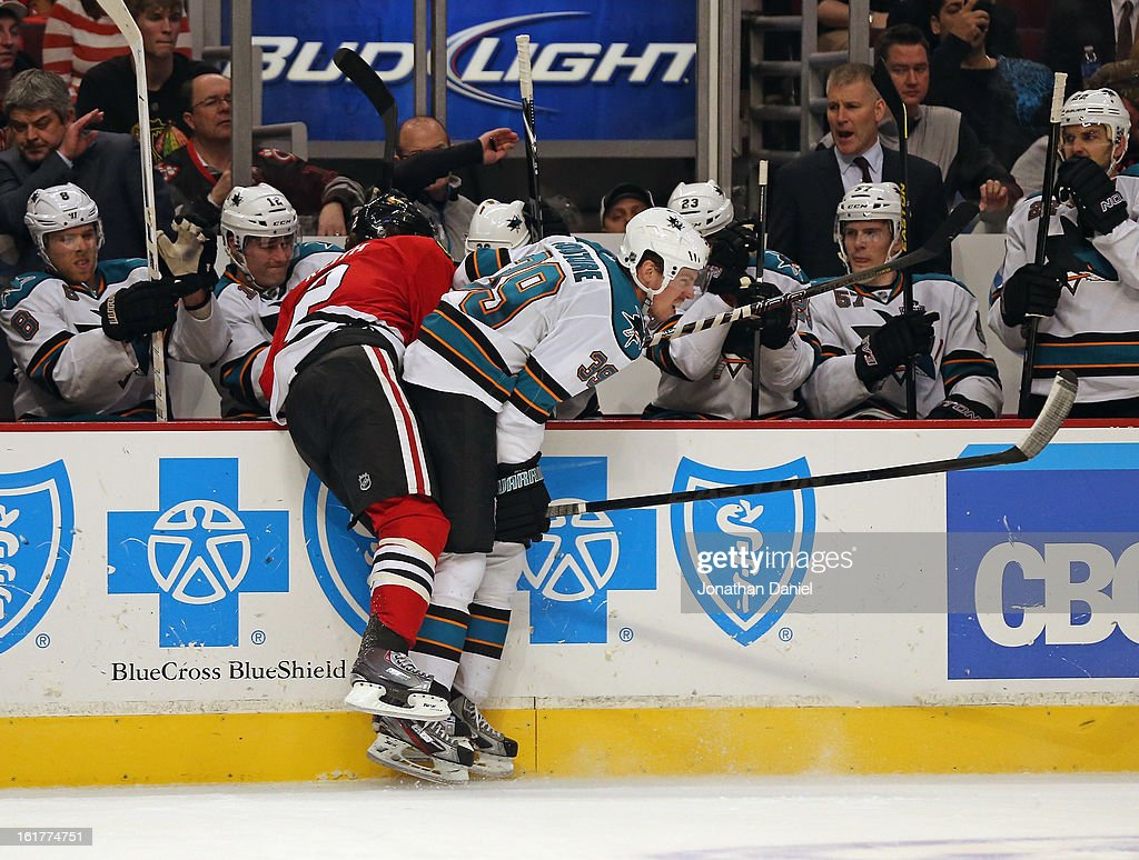 Logan Couture #39 of the San Jose Sharks knocks Duncan Keith #2 of the Chicago Blackhawks over the boards in front of the Shark bench at the United Center on February 15, 2013 in Chicago, Illinois.