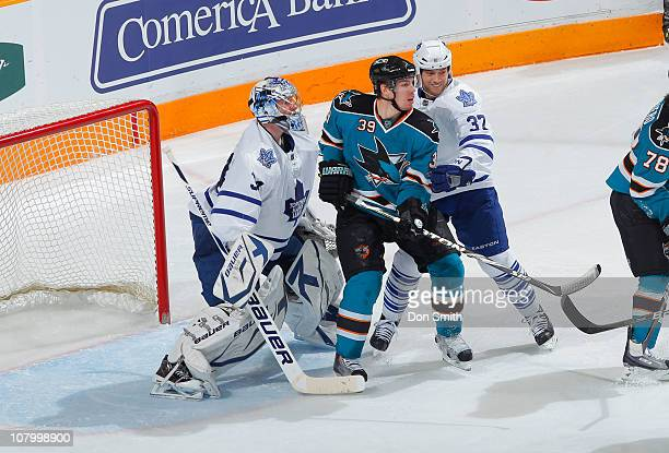 Logan Couture of the San Jose Sharks looks for the puck against James Reimer and Tim Brent of the Toronto Maple Leafs during an NHL game on January...
