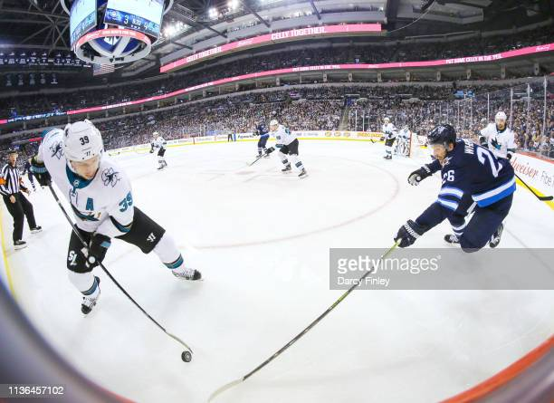 Logan Couture of the San Jose Sharks plays the puck away from Blake Wheeler of the Winnipeg Jets during third period action at the Bell MTS Place on...
