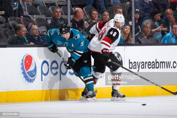 Logan Couture of the San Jose Sharks skates after the puck against Jordan Martinook of the Arizona Coyotes at SAP Center on February 13 2018 in San...
