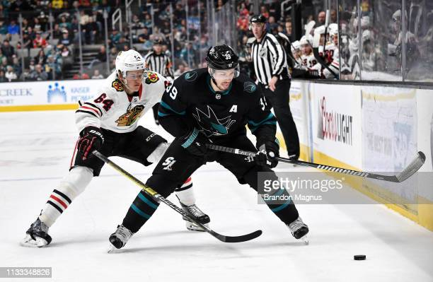 Logan Couture of the San Jose Sharks skates ahead after the puck against David Kampf of the Chicago Blackhawks at SAP Center on March 28 2019 in San...