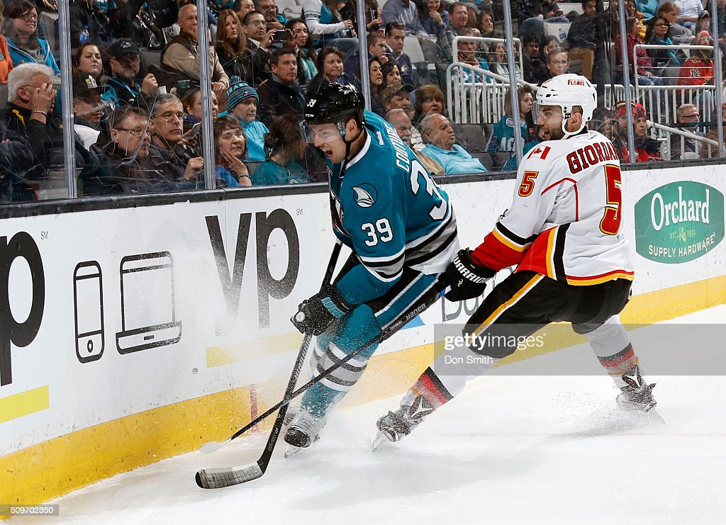 Logan Couture #39 of the San Jose Sharks skates past Mark Giordano #5 of the Calgary Flames during a NHL game at the SAP Center at San Jose on February 11, 2016 in San Jose, California.