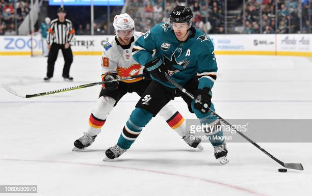 Logan Couture of the San Jose Sharks skates the puck ahead of Elias Lindholm of the Calgary Flames at SAP Center on November 11 2018 in San Jose...