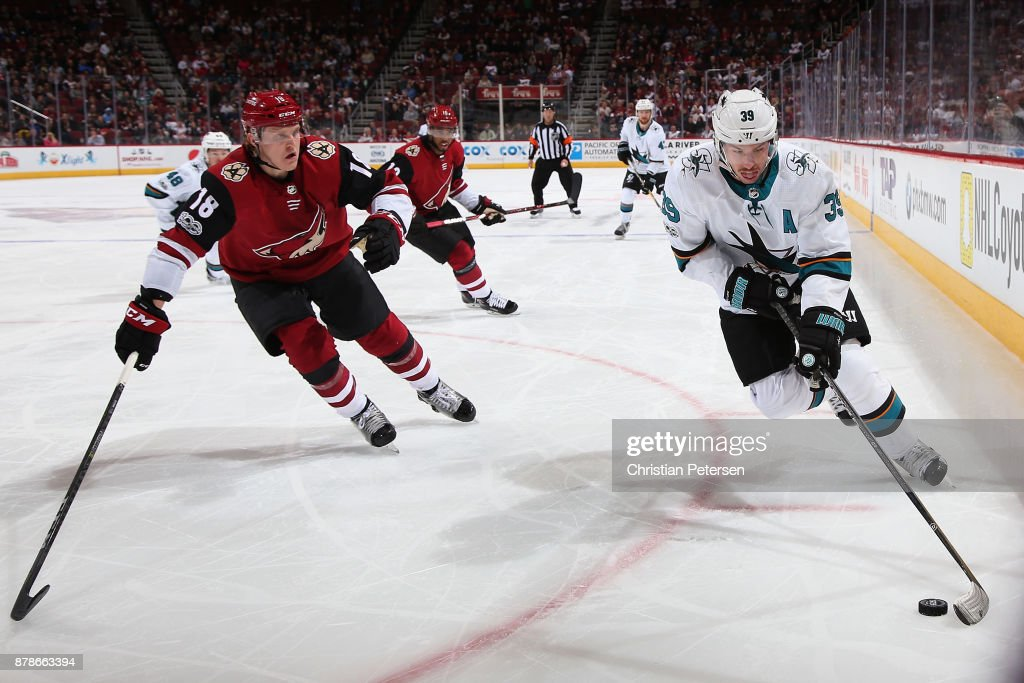 Logan Couture #39 of the San Jose Sharks skates with the puck ahead of Christian Dvorak #18 of the Arizona Coyotes during the third period of the NHL game at Gila River Arena on November 22, 2017 in Glendale, Arizona. The Sharks defeated the Coyotes 3-1.