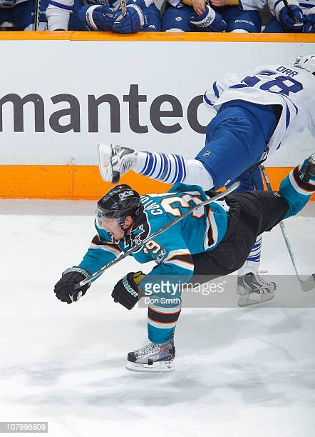 Logan Couture of the San Jose Sharks takes a hit by Colton Orr of the Toronto Maple Leafs during an NHL game on January 11, 2011 at HP Pavilion at...