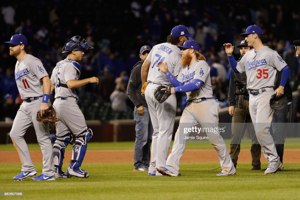 Logan Forsythe #11, Austin Barnes #15, Kenley Jansen #74, Justin Turner #10 and Cody Bellinger #35 of the Los Angeles Dodgers celebrate defeating the Chicago Cubs 6-1 in game three of the National League Championship Series at Wrigley Field on October 17, 2017 in Chicago, Illinois.