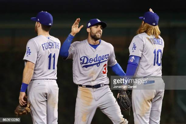 Logan Forsythe, Chris Taylor, and Justin Turner of the Los Angeles Dodgers celebrate after beating the Chicago Cubs 6-1 during game three of the...