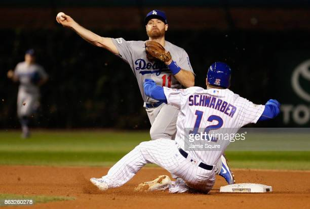 Logan Forsythe of the Los Angeles Dodgers attempts to turn a double play past Kyle Schwarber of the Chicago Cubs in the sixth inning during game five...