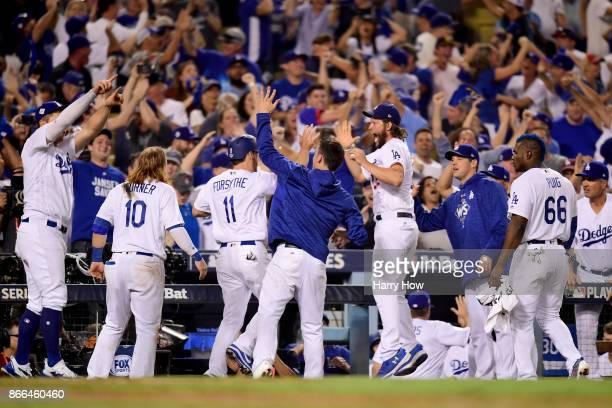 Logan Forsythe of the Los Angeles Dodgers celebrates with teammates after scoring a run on a RBI single hit by Enrique Hernandez to tie the game 55...