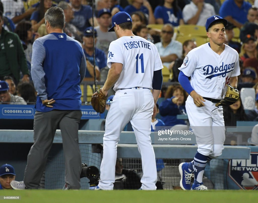 Logan Forsythe #11 of the Los Angeles Dodgers leaves the field with right shoulder discomfort as he is replaced by Enrique Hernandez #14 of the Los Angeles Dodgers in the sixth inning of the game against the Arizona Diamondbacks at Dodger Stadium on April 14, 2018 in Los Angeles, California.