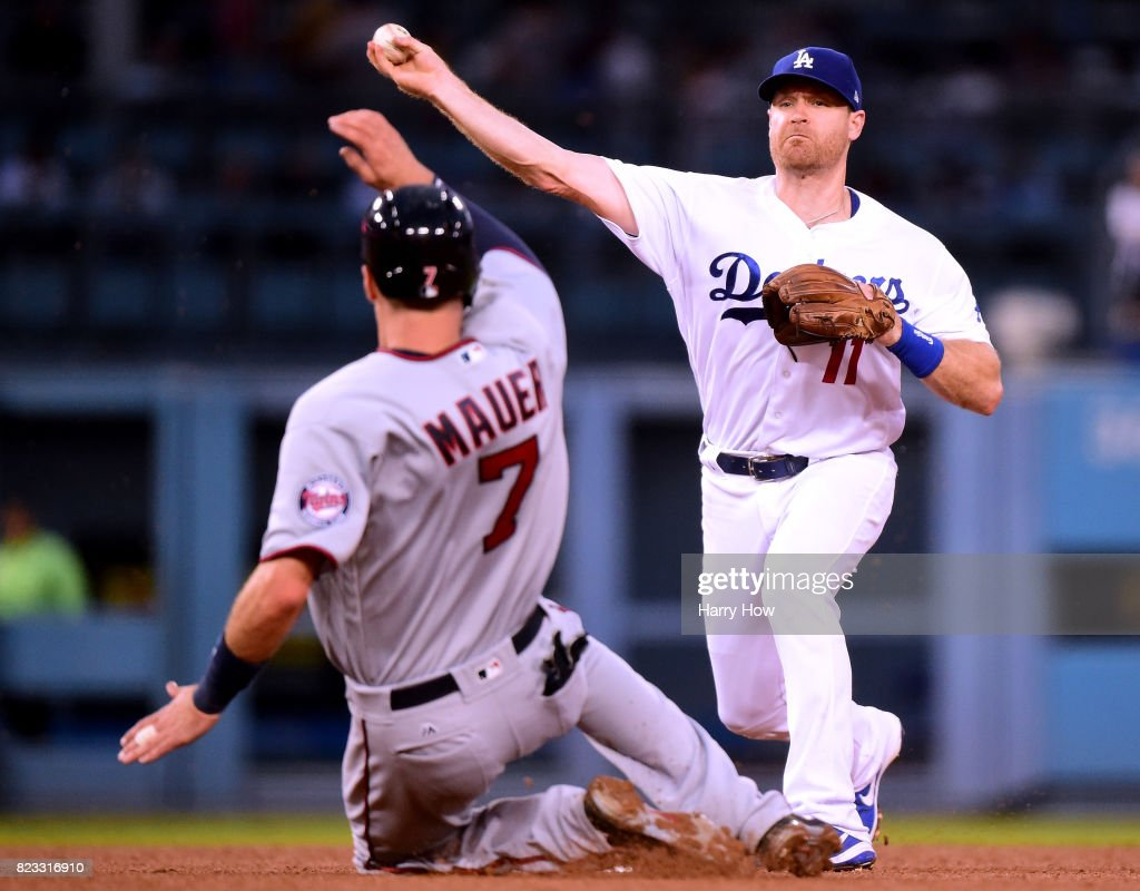 Logan Forsythe #11 of the Los Angeles Dodgers makes a throw over Joe Mauer #7 of the Minnesota Twins for a double play during the fourth inning at Dodger Stadium on July 24, 2017 in Los Angeles, California.