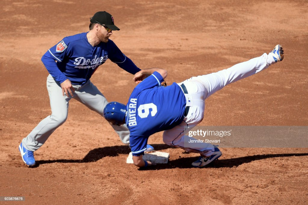 Logan Forsythe #11 of the Los Angeles Dodgers makes the tag on Drew Butera #9 of the Kansas City Royals at Surprise Stadium on February 24, 2018 in Surprise, Arizona.